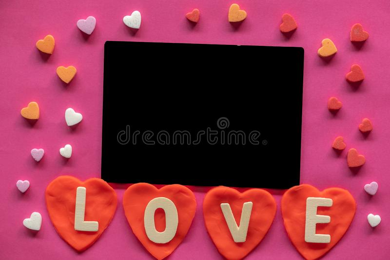 Many hearts around Blackboard with word LOVE on pink background, Love icon, valentine`s day, relationships concept. With copy space stock images