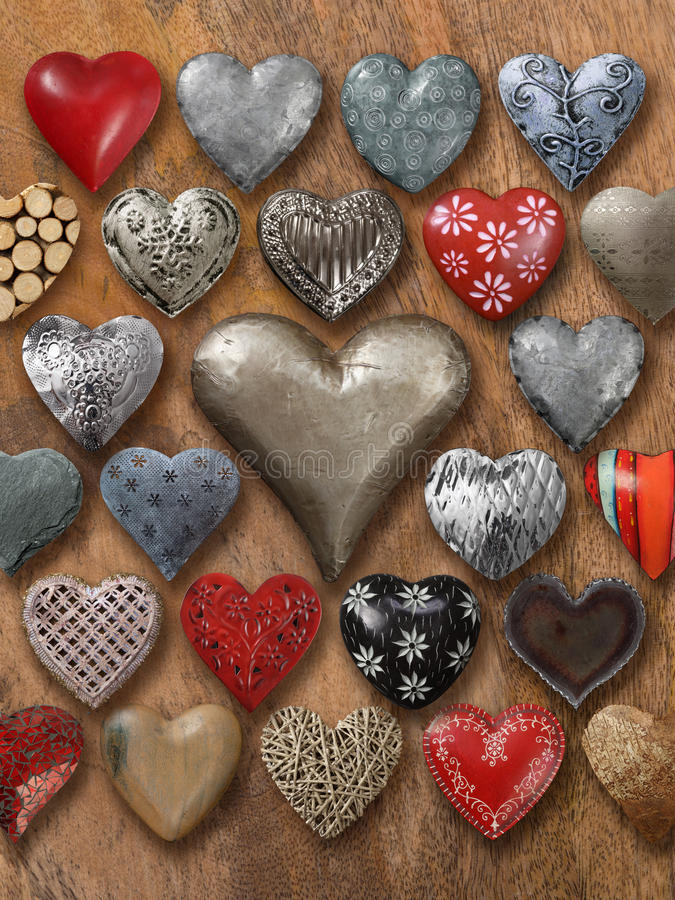 Many hearts on wood background. Photos of many heart-shaped things made of stone, metal and wood on wood background stock photos