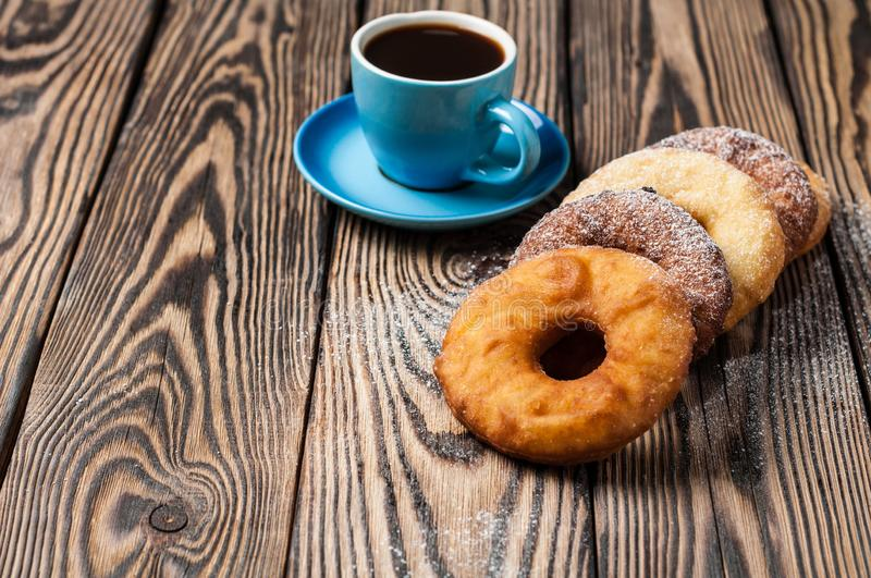Many homemade baked donuts without cream sprinkled of powdered sugar near full cup of hot black coffee lies on rustic wooden t royalty free stock images