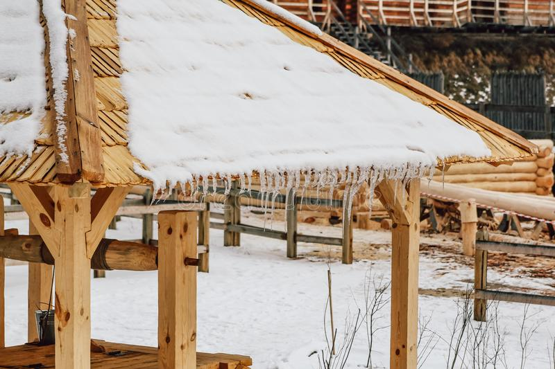 Many icicles melt on the wooden roof with water drops. Spring is comming. Many beautiful icicles melt on the wooden roof at the end of winter and water drops royalty free stock photos