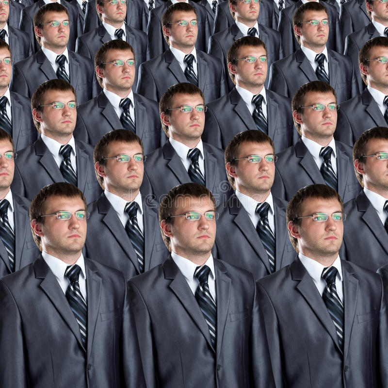 Many identical businessmen clones. Many identical businessman clones. Businessman production concept stock photography