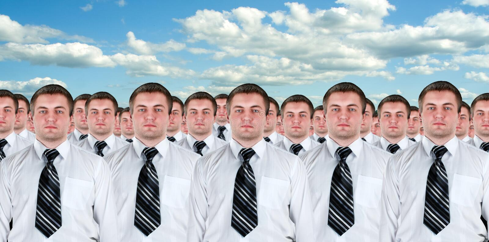 Many identical businessmen clones. Many identical businessman clones. Businessman production concept royalty free stock photography