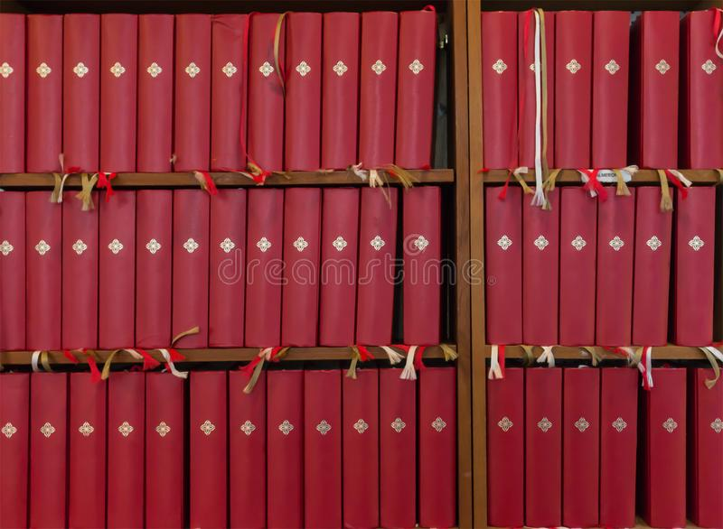 Many identical red books with bookmarks on the shelf royalty free stock images
