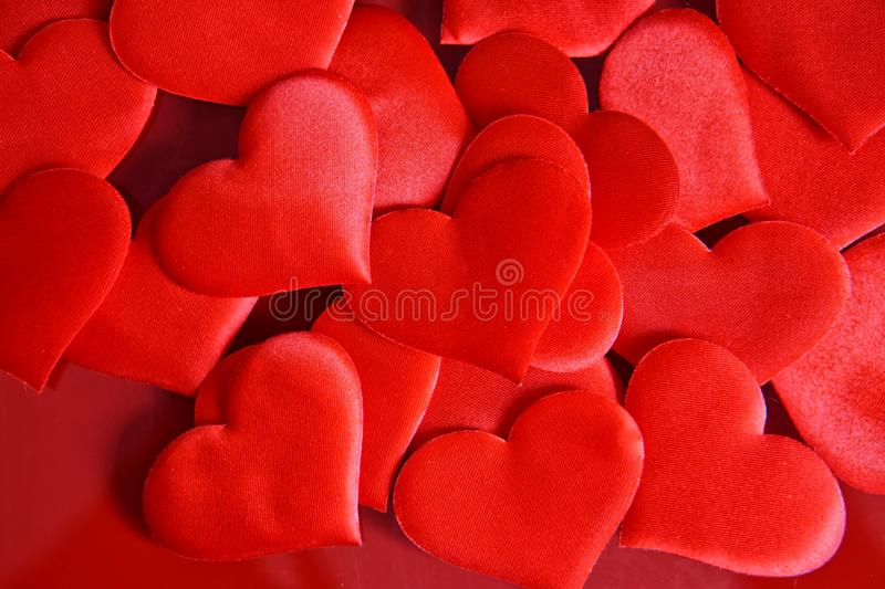 Many identical red hearts on a red surface. St. Valentine`s Day. Congratulations on Valentine`s Day stock photography