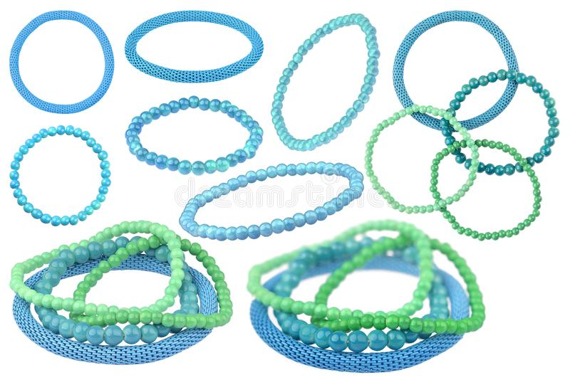 Many instances of blue and green elastic bracelets made of pearl-like round beads and one blue metallic elastic bracelet, isolated. On white background stock image