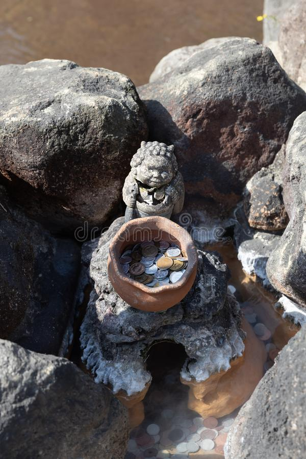Many Japanese coins in pond with clay jar and statue royalty free stock images
