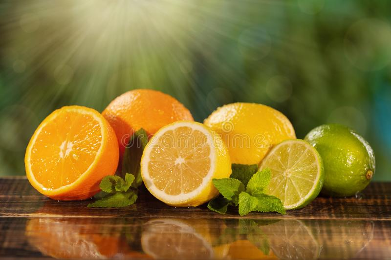 Many juicy citrus fruits on wet wooden boards, in the sunlight, with mint and water drops, concept. Many juicy citrus fruits on wet wooden boards, in the stock images
