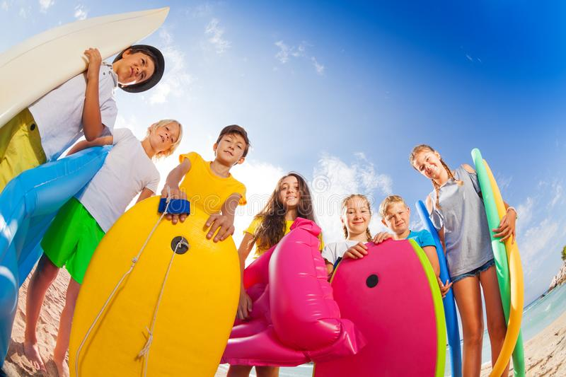 Many kids on beach with swimming stuff stock photography