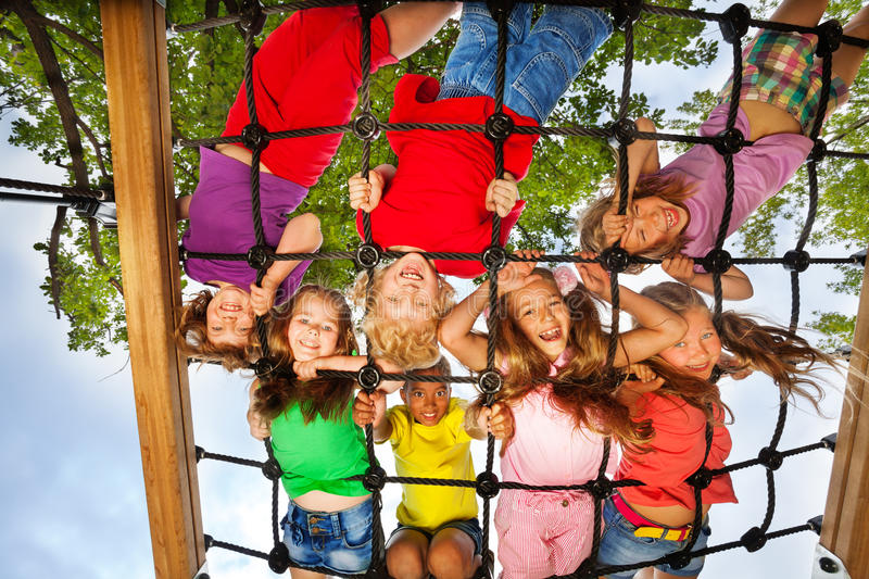Many kids look though gridlines of playground. And smile happily royalty free stock photos