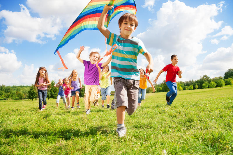 Many kids run with kite. Many happy kids run together with kite on sunny summer day stock image
