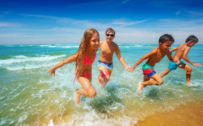 Many kids run from sea waves holding hands smiling royalty free stock photography