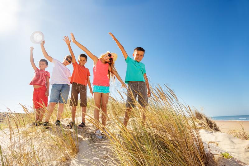 Many kids on the sand beach happy wave hands up stock image