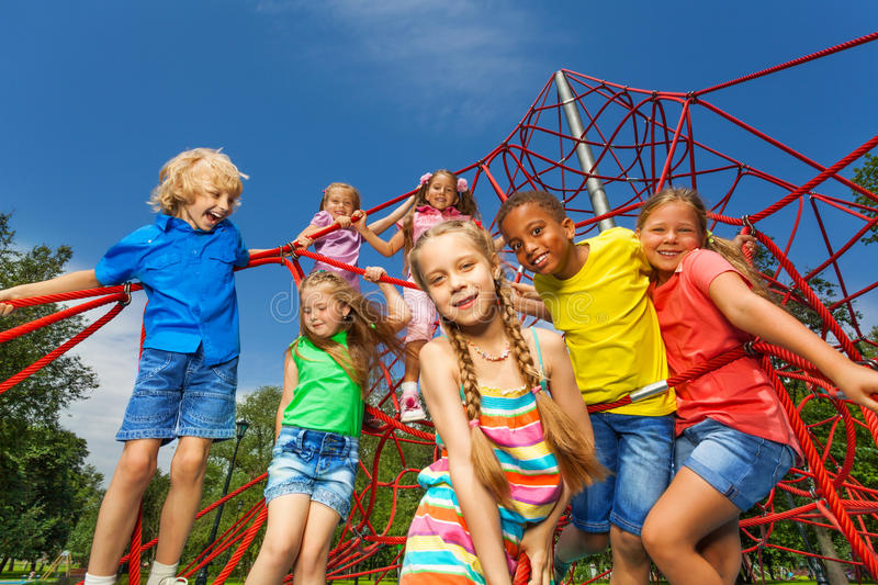Many kids stand on red ropes together in park stock photography