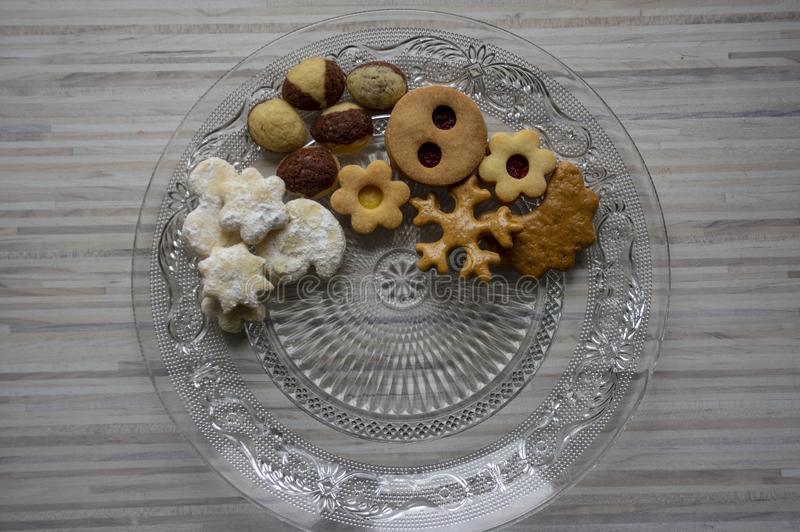 Many kinds of Christmas cookies on cut glass transparent plate, sweet food on wooden table. Partially occupied stock photo