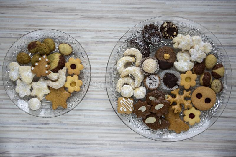 Many kinds of Christmas cookies on two cut glass transparent plates, sweet food on wooden table. Many kinds of Christmas cookies on cut glass transparent plates stock photo