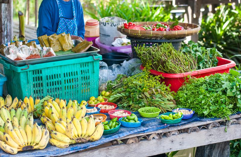 Many kinds of vegetable are places on the stall with ripe bananas waiting to be sold in Thailand organic market stock photo