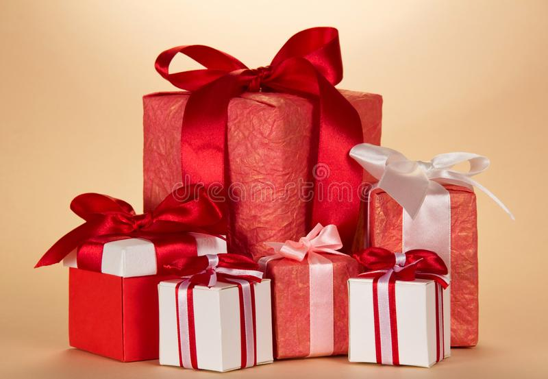 Many large and small Christmas gifts on beige royalty free stock photo