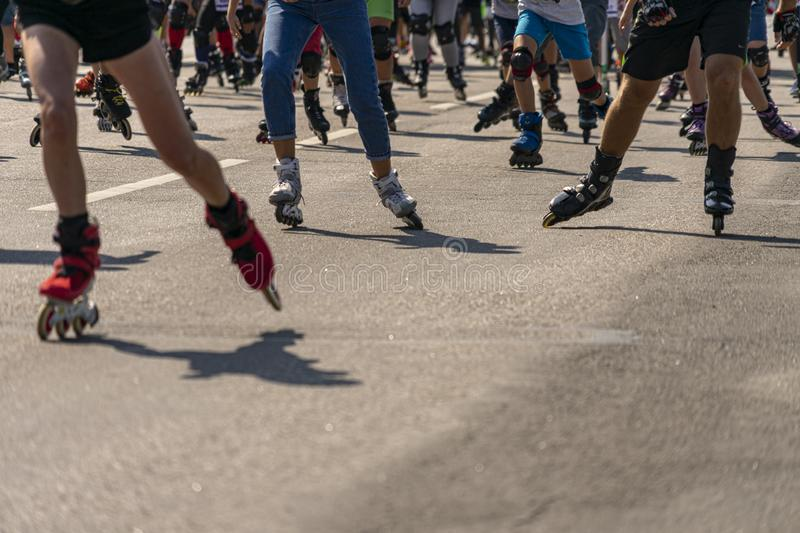 Many legs in roller-blades. People participate in outdoors racing marathon stock images