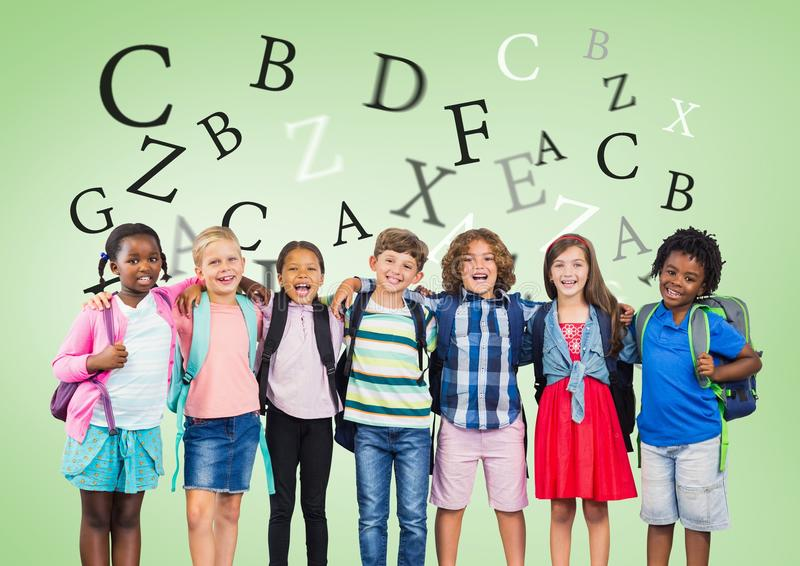 Many letters around Multicultural School kids in front of green background stock photo