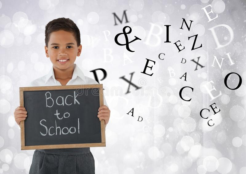 Many letters around Schoolboy holding back to school blackboard in front of bright bokeh background stock photo