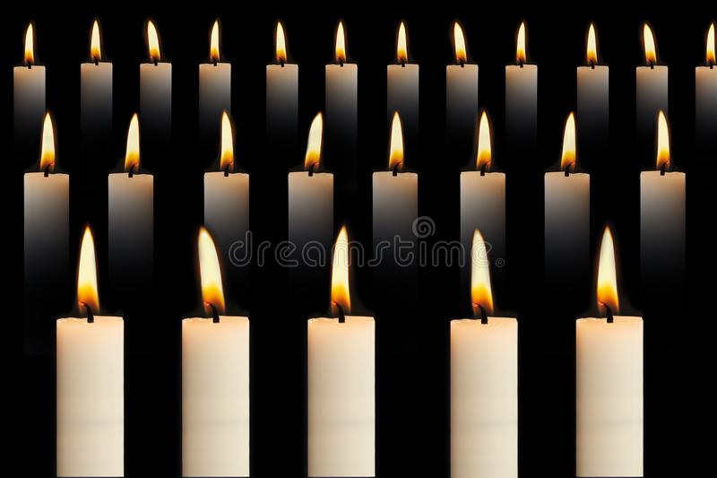Many lit candles in rows on black background. Faith, religion, honor or spirituality concept. stock photography