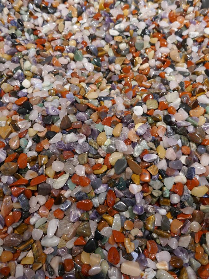Many little colorful stones. Colorful mix of polished gemstones and minerals. Close-up royalty free stock photo