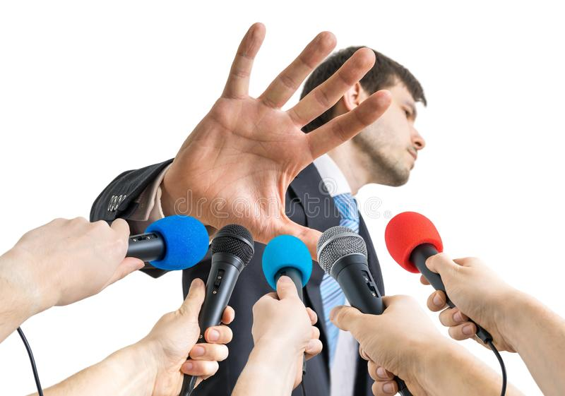 Many microphones in front of politician who shows no comment gesture royalty free stock image