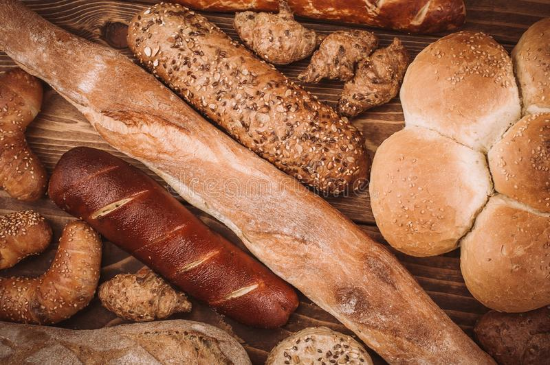 Many mixed baked breads and rolls on rustic wooden table stock photos