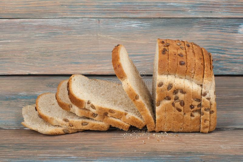 Many mixed breads and rolls of baked bread on wooden table background. stock photography