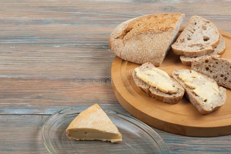 Many mixed breads and rolls of baked bread on wooden table background. stock images