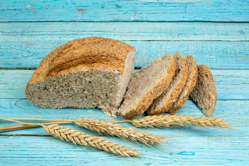 Many mixed breads and rolls of baked bread on wooden table background. ears of wheat stock images