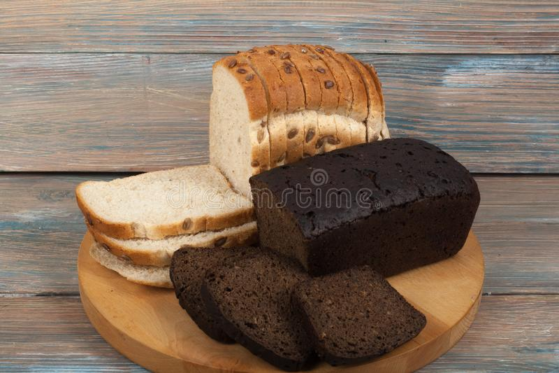 Many mixed breads and rolls of baked bread on wooden table background. royalty free stock photography