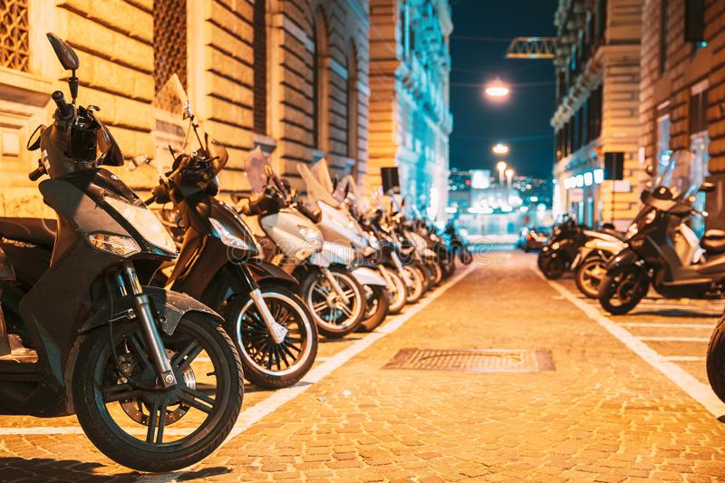 Many Motorbikes, Motorcycles Parked In City. Scooters Parked On Night Street In European City royalty free stock image