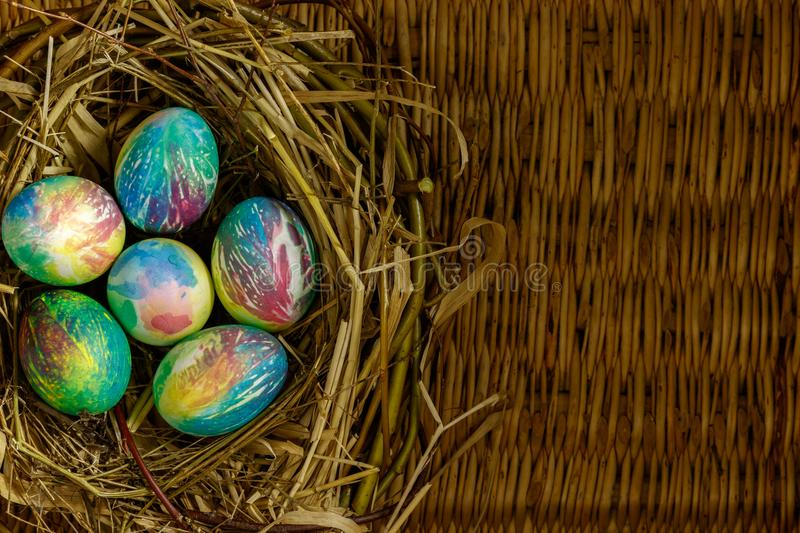 Many multi-colored Easter eggs lie in a nest of dry grass and twigs. Nest with eggs lie on the background of a table made of wicke royalty free stock photography