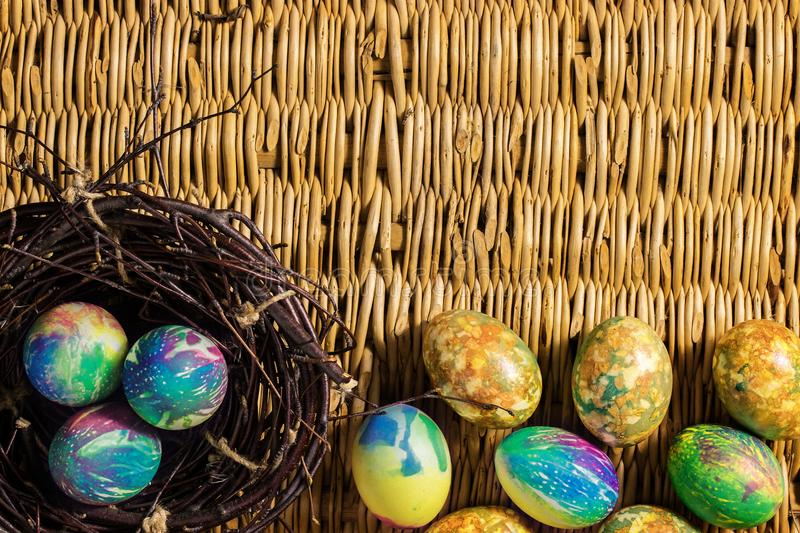 Many multi-colored Easter eggs. Three eggs lie in a nest of branches. The rest of the Easter eggs lie on the background of a table royalty free stock photo
