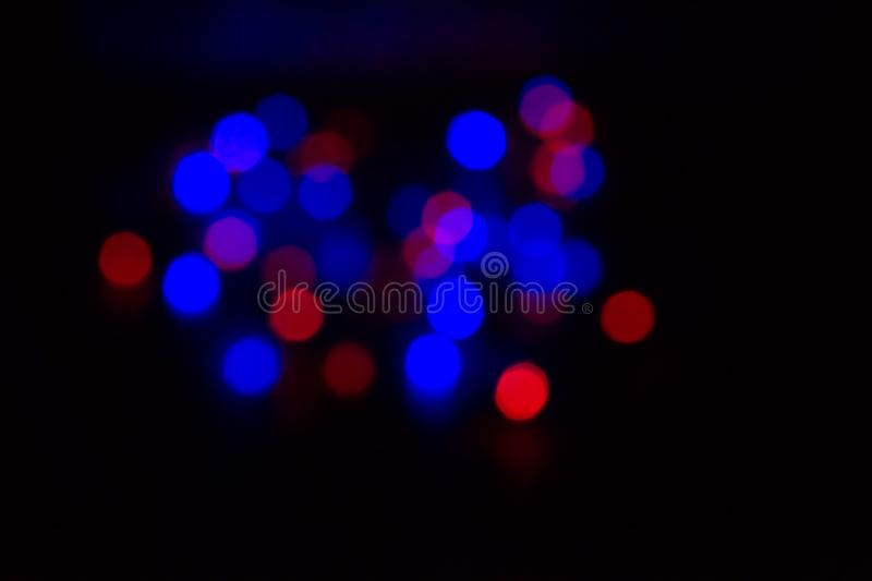 Many multicolored blurry lights red, blue, glowing in the dark stock photography