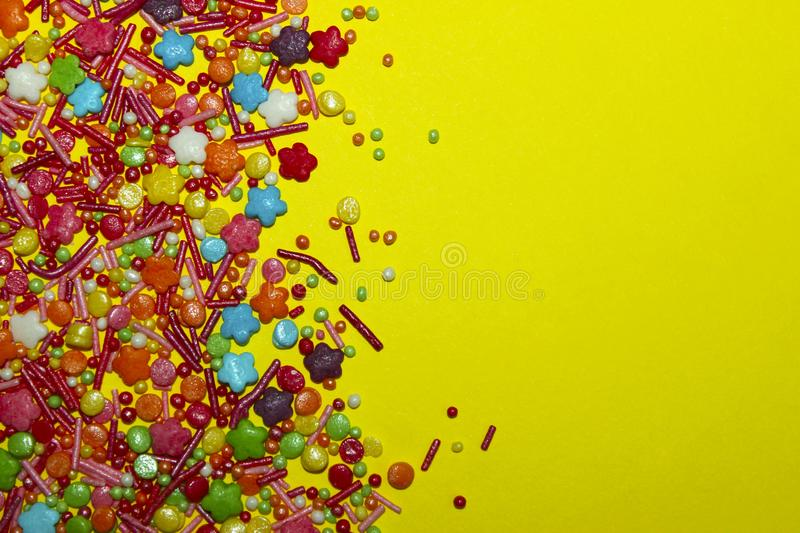 Many Multicolored Candy Sweets On Yellow Background. stock photography