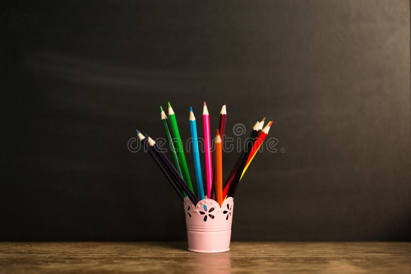 Many multicolored pencils in glass on wooden table with black background. Back to school concept stock photography