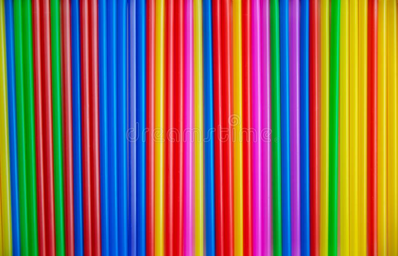 Many multicolored tubes for a cocktail copy. Plastic material, plastic tubing for drinking liquid. Background stock image