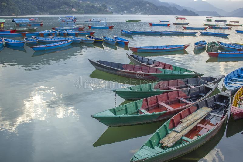 multicolored wooden boats on the lake against the backdrop of green mountains. blue red green yellow empty boats on the water royalty free stock photos