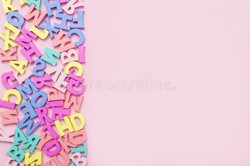 Many multicolored wooden letters on a pink background. toy letters. english alphabet. View from above. Flat lay. Copy space for te. Xt royalty free stock photography