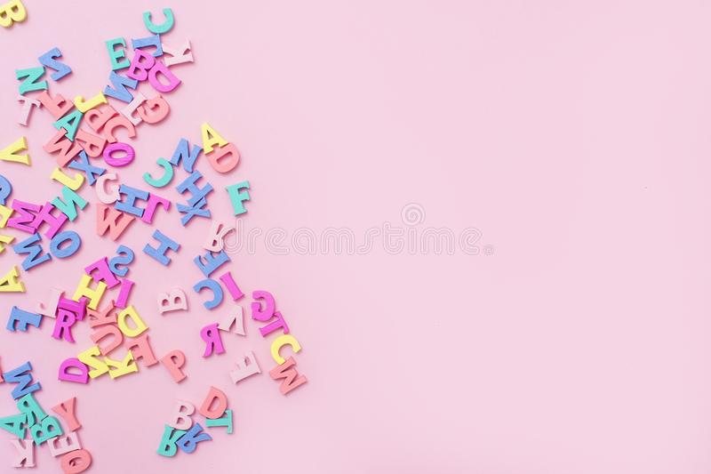 Many multicolored wooden letters on a pink background. toy letters. english alphabet. View from above. Flat lay. Copy space for te. Xt stock image