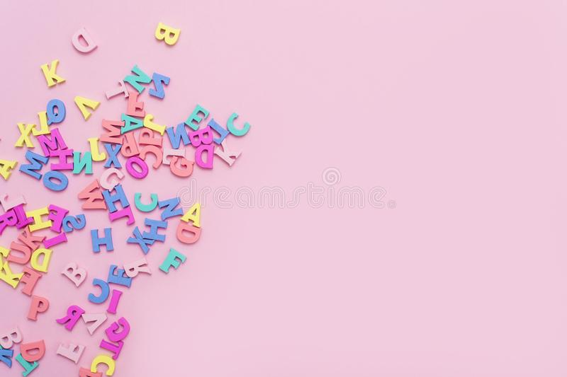 Many multicolored wooden letters on a pink background. toy letters. english alphabet. View from above. Flat lay. Copy space for te. Xt stock photos