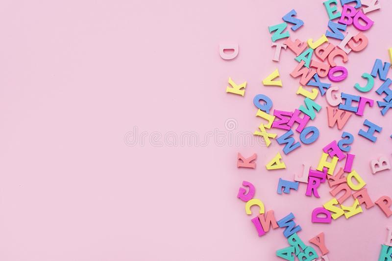 Many multicolored wooden letters on a pink background. toy letters. english alphabet. View from above. Flat lay. Copy space for te. Xt stock photography