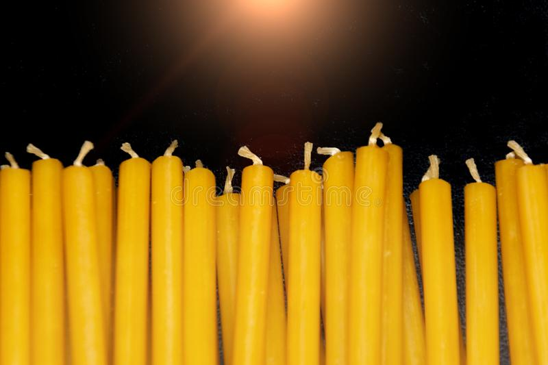 Many natural thin yellow wax candles lie on black background. royalty free stock photos