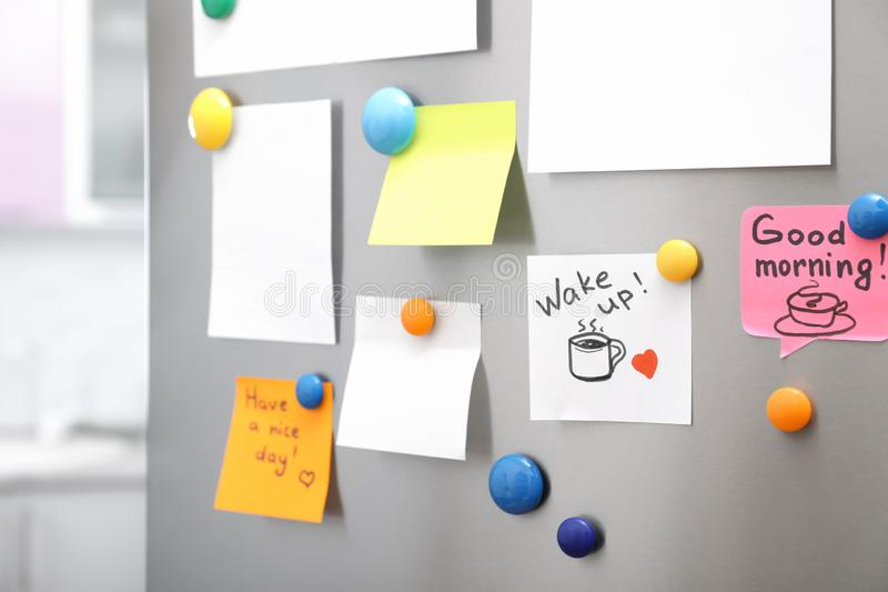 Many notes and empty sheets with magnets on refrigerator door in kitchen. Space for text royalty free stock photography