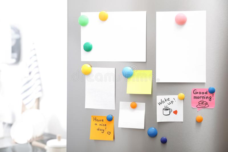 Many notes and empty sheets with magnets on refrigerator door in kitchen. Space for text royalty free stock images