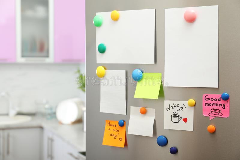 Many notes and empty sheets with magnets on refrigerator door in kitchen. Space for text royalty free stock photos