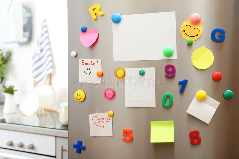 Many notes and empty sheets with magnets on refrigerator door in kitchen. Space for text stock photography