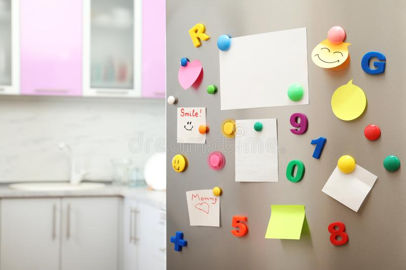 Many notes and empty sheets with magnets on refrigerator door in kitchen. Space for text royalty free stock image